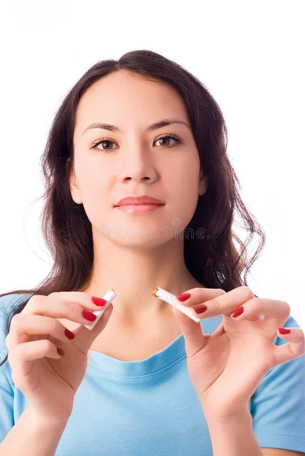 Junge Frau, die eine Zigarette bricht lizenzfreies stockfoto