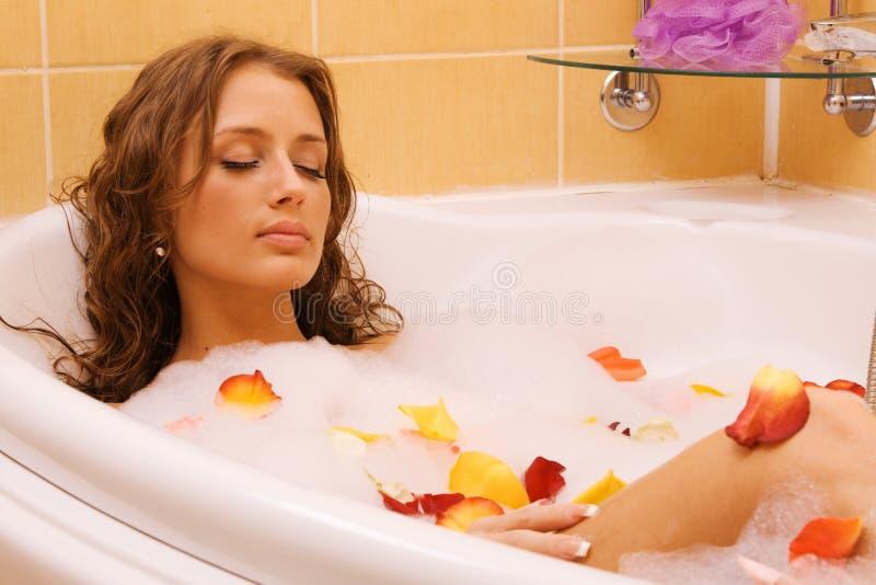 Junge Frau, die in einem Bad sich entspannt stockfoto