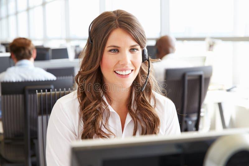 Junge Frau, die in einem Call-Center, Schirm betrachtend arbeitet stockbild