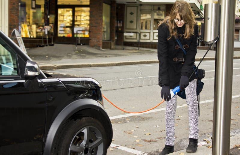 Junge Frau, die in einem elektrischen Auto einsteckt stockfotos