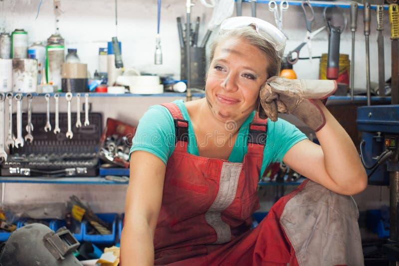 Junge Frau, die in einem Mechanikershop aufwirft lizenzfreie stockbilder