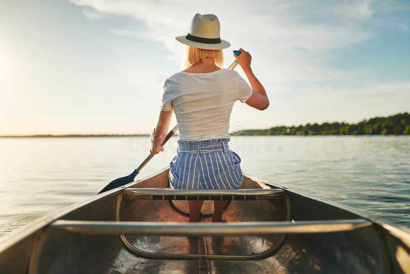 Junge Frau, die an einem sonnigen Nachmittag im Sommer canoeing ist stockbild