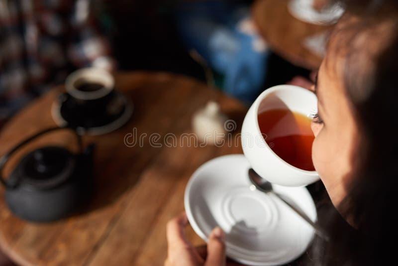 Junge Frau, die in einem trinkenden Tee des Cafés sitzt lizenzfreies stockfoto