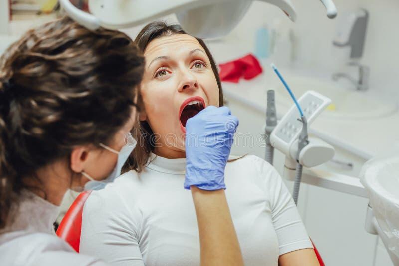 Junge Frau, die in einem zahnmedizinischen Stuhl für Ernennung eines Doktors sitzt Während dieser Zeit war sie über Furcht sehr b stockfotos