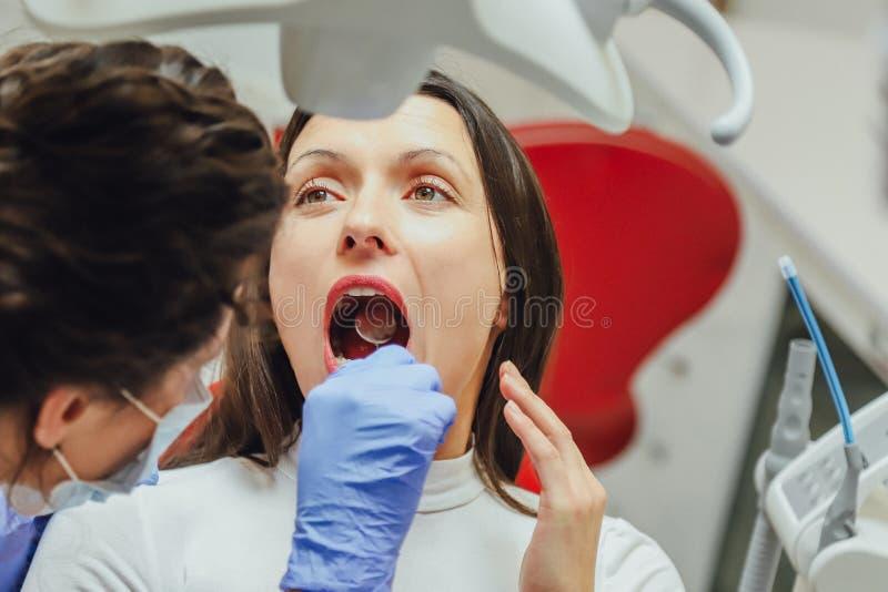 Junge Frau, die in einem zahnmedizinischen Stuhl für Ernennung eines Doktors sitzt Während dieser Zeit war sie über Furcht sehr b stockbild