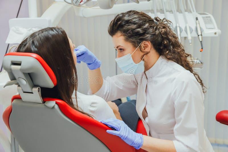 Junge Frau, die in einem zahnmedizinischen Stuhl für Ernennung eines Doktors sitzt Während dieser Zeit war sie über Furcht sehr b lizenzfreie stockfotos