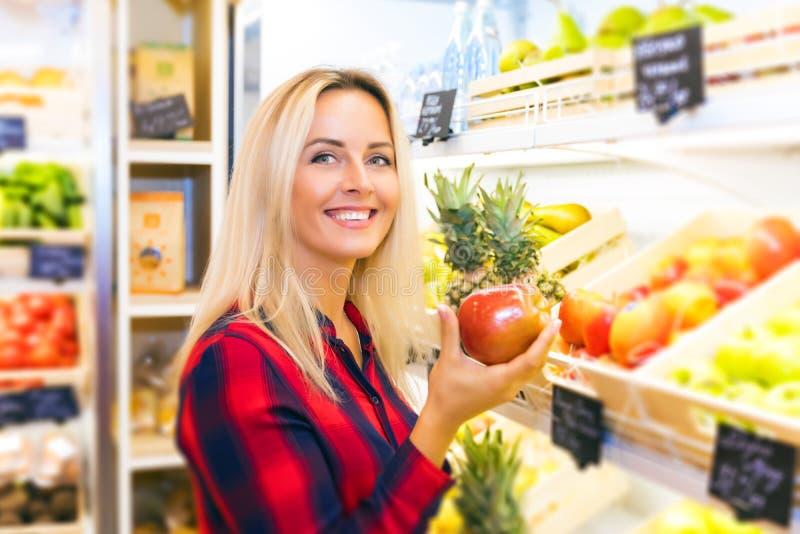 Junge Frau, die einen Apfel in ihrer Hand am Lebensmittelgeschäft hält lizenzfreies stockbild