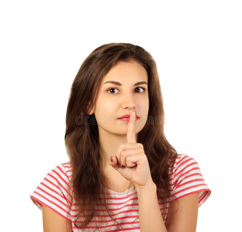 Junge Frau, die einen Finger auf ihren Lippen - stille Geste hält emotionales Mädchen lokalisiert auf weißem Hintergrund lizenzfreie stockfotografie