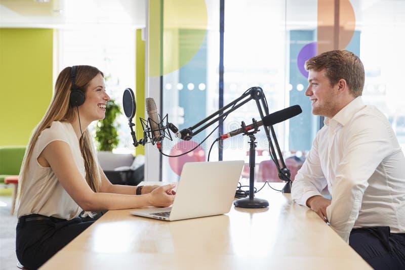 Junge Frau, die einen Gast in einem Studio für einen Podcast interviewt stockfotos