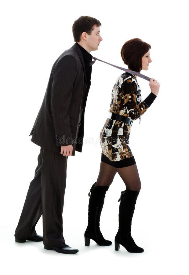 Junge Frau, die einen jungen Mann in einer Gleichheit, getrennt zieht stockfotos