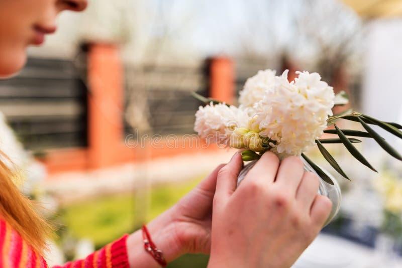 Junge Frau, die einen kleinen Hyazinthenblumenstrauß herstellt lizenzfreie stockfotos