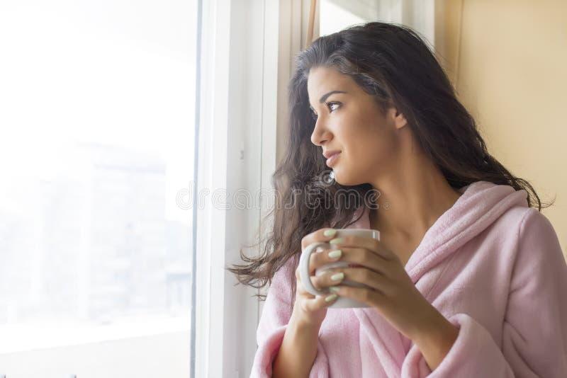 Junge Frau, die einen Morgenkaffee trinkt lizenzfreies stockbild