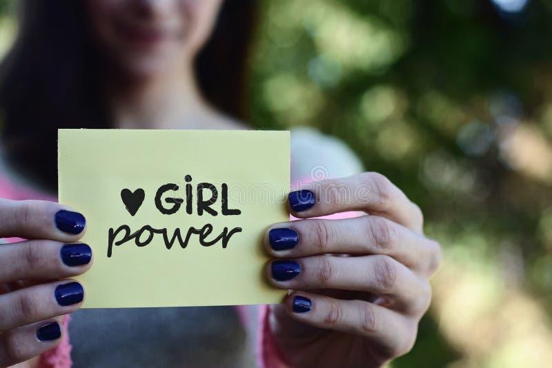 Junge Frau, die einen Notizblock mit Mädchenenergietext zeigt lizenzfreies stockfoto