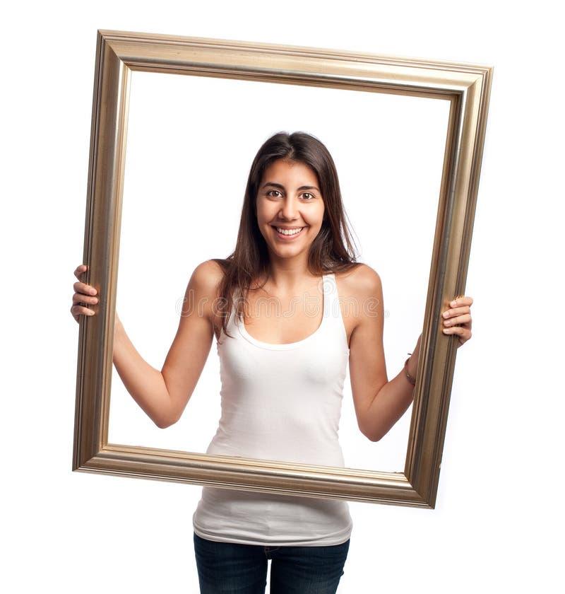 Junge Frau, die einen Rahmen hält stockbilder