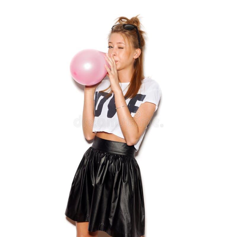 Junge Frau, die einen rosa Ballon durchbrennt lizenzfreie stockfotos