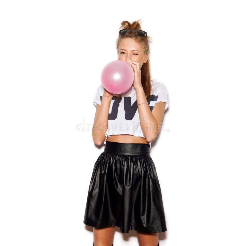 Junge Frau, die einen rosa Ballon durchbrennt lizenzfreies stockbild