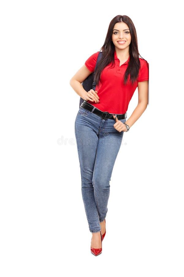 Junge Frau, die einen Rucksack und eine Aufstellung trägt stockfotos