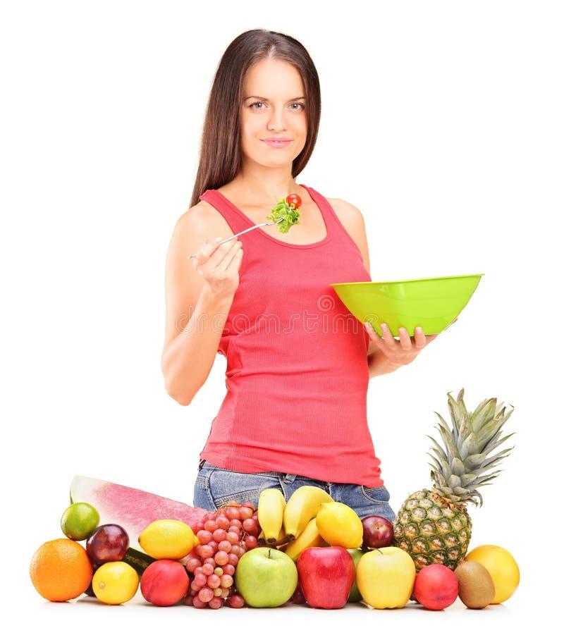 Junge Frau, die einen Salat isst lizenzfreie stockfotografie