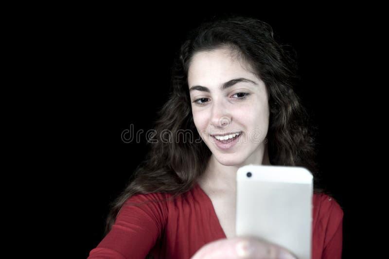 Junge Frau, die einen Smartphone hält stockfoto