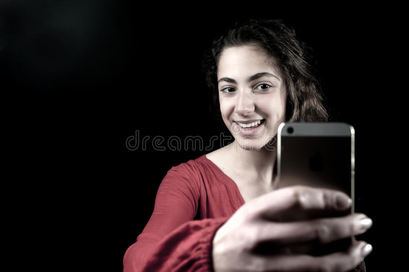 Junge Frau, die einen Smartphone hält stockbild