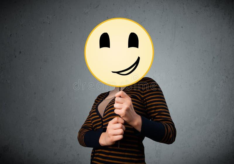 Junge Frau, die einen smileygesicht Emoticon hält stockbild