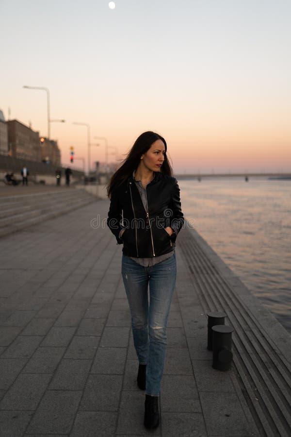 Junge Frau, die einen Sonnenuntergangweg entlang dem Fluss Daugava mit einer Ansicht über klaren blauen Himmel genießt lizenzfreie stockbilder