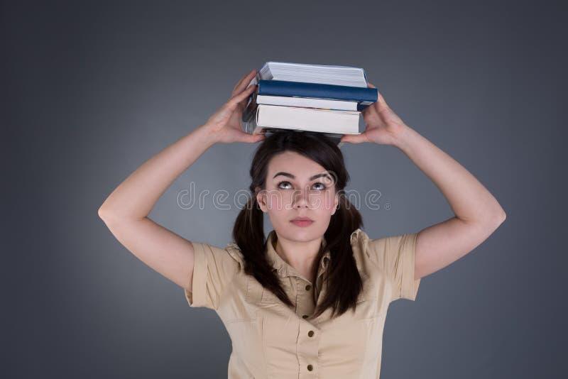 Junge Frau, die einen Stapel Bücher auf ihrem Kopf hält lizenzfreie stockbilder