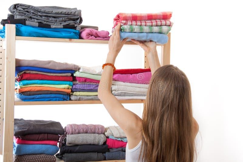Junge Frau, die einen Stapel von Kleidung hält stockfotografie