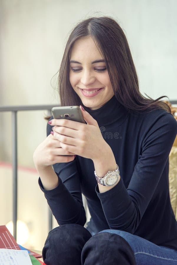 Junge Frau, die einen Tasse Kaffee genießt und an ihrem Telefon spricht stockfotografie