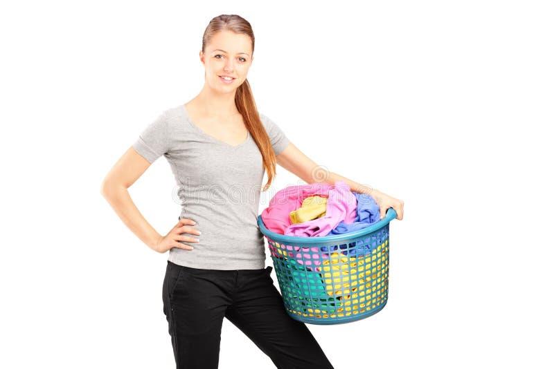 Junge Frau, die einen Wäschereikorb anhält lizenzfreie stockfotos