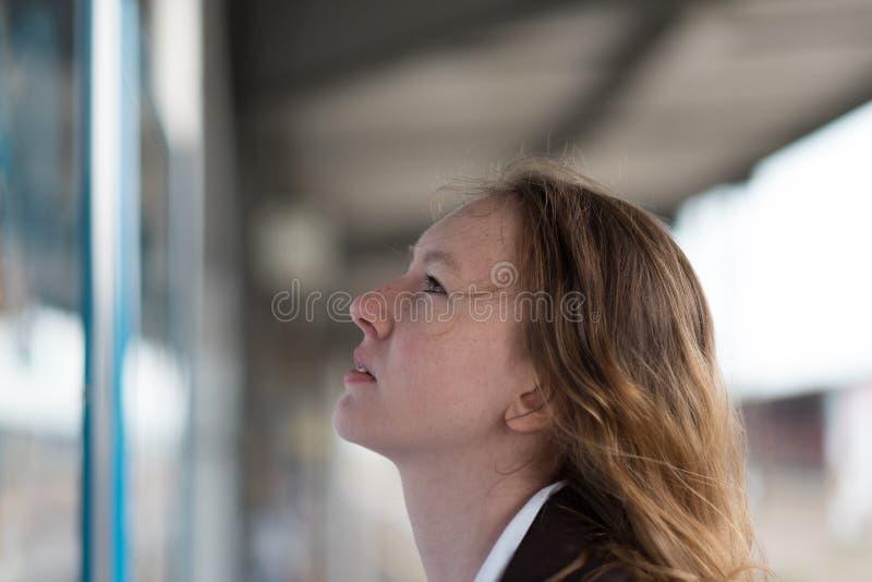 Junge Frau, die einen Zeitplan überprüft stockfotografie