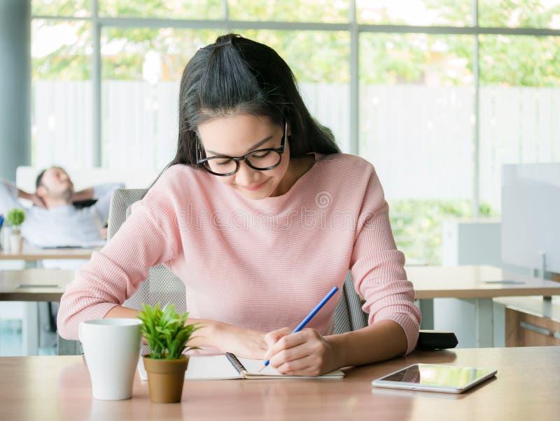 Junge Frau, die an einer Erwachsenenbildungsklasse studieren oder glückliche junge Frau, die Organisator zum Notizbuch tuend arbe lizenzfreie stockfotos