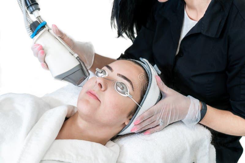 Junge Frau, die einer Laser-Hautbehandlung für die nicht-Ablativhaut erneuert, um Falten, Aknenarben und andere Gesichtsbehandlun lizenzfreie stockfotos