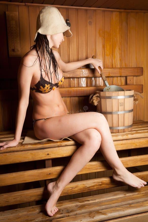 Junge Frau, die in einer Sauna sich entspannt stockbild