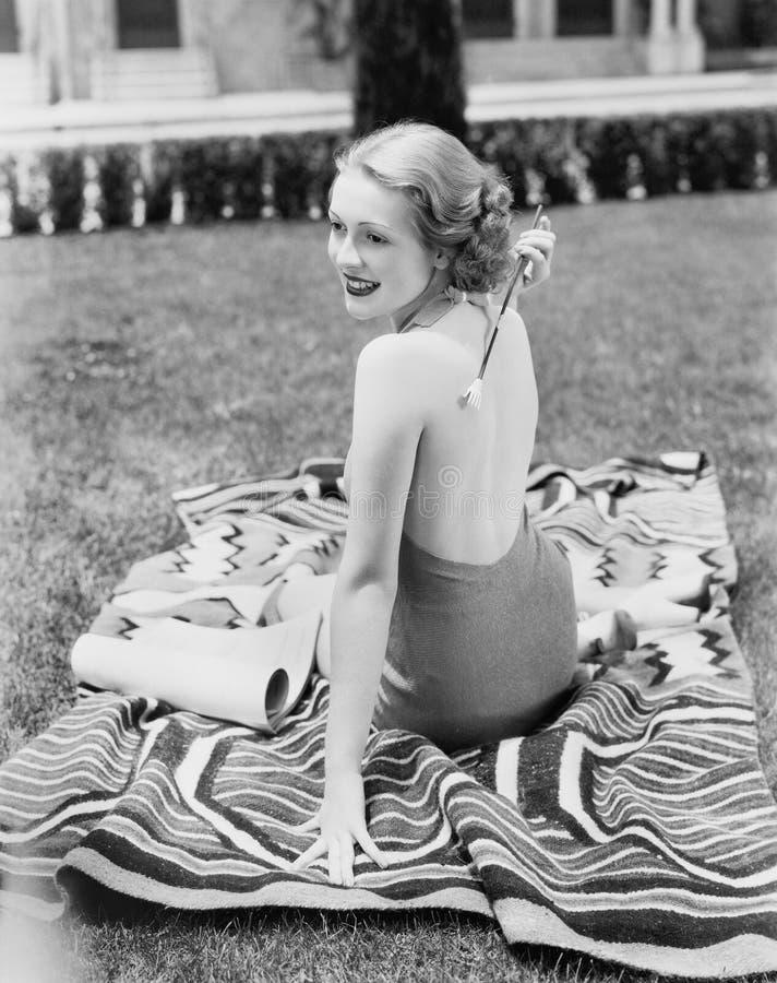 Junge Frau, die in einer Sonnenklage auf einem Rasen zurück verkratzt sie sitzt (alle dargestellten Personen sind nicht längeres  lizenzfreies stockbild