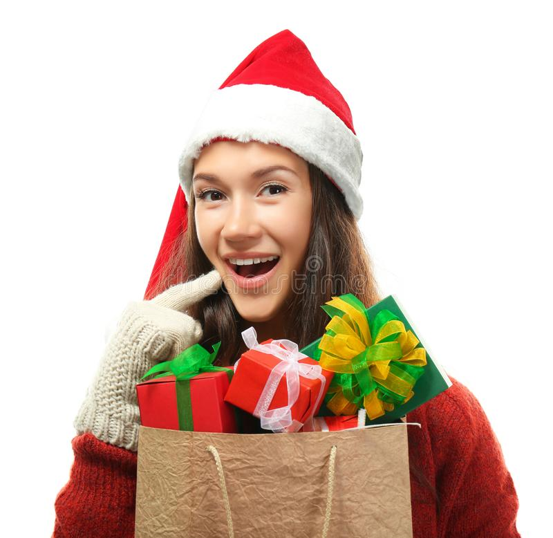 Junge Frau, die Einkaufstasche mit Weihnachtsgeschenken auf weißem Hintergrund hält stockbilder