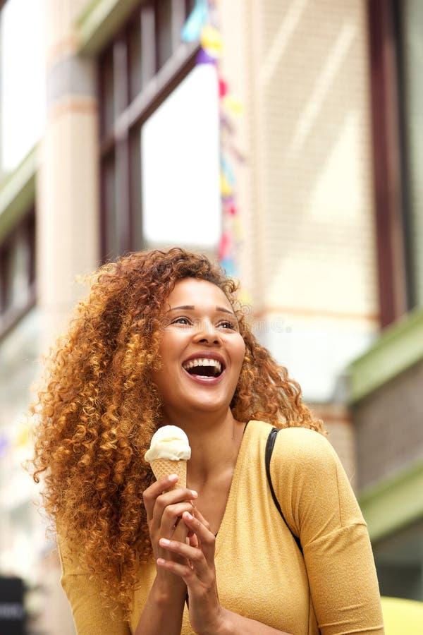 Junge Frau, die Eiscreme in der Stadt isst stockfotografie