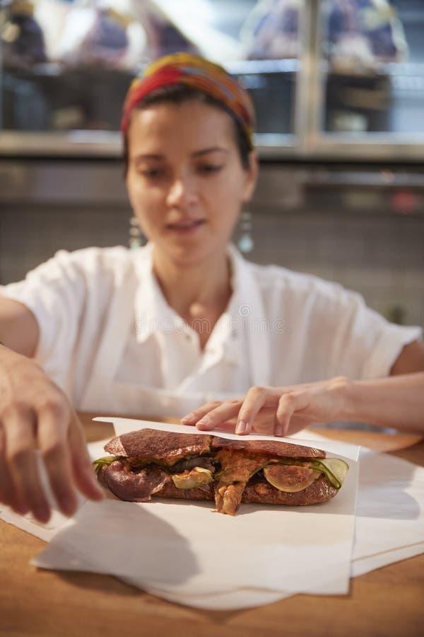 Junge Frau, die entgegengesetzt ein Sandwich an Feinkostgeschäft, vertikal einwickelt lizenzfreies stockbild