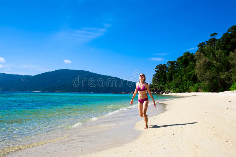 Junge Frau, die entlang den Strand läuft stockfotografie