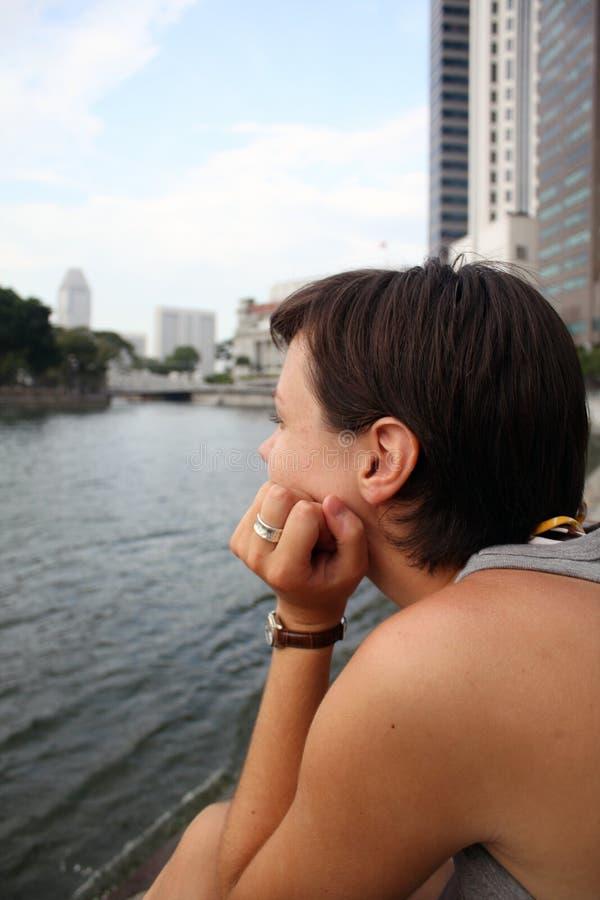 Junge Frau, die entlang der anderen Seite des Flusses anstarrt stockbilder