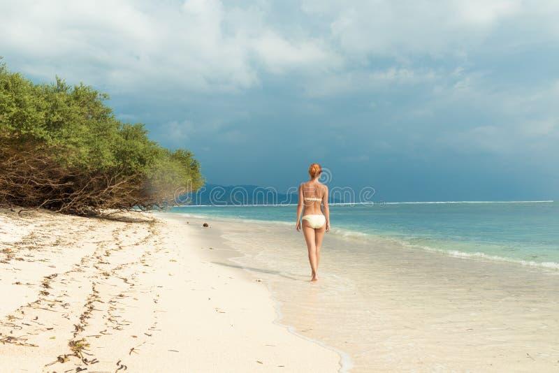 Junge Frau, die entlang tropischen Strand geht lizenzfreie stockfotografie