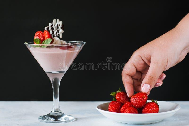 Junge Frau, die Erdbeere von weniger Untertasse nimmt stockbild