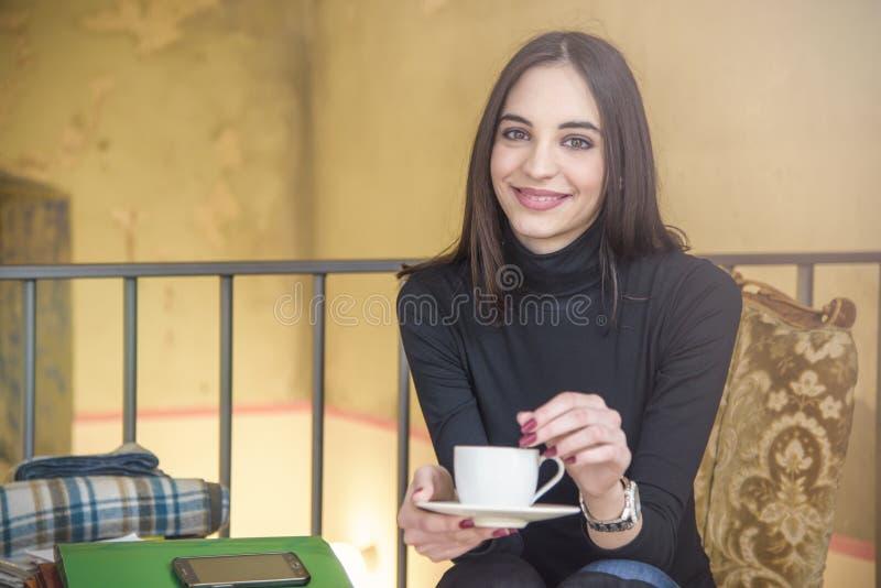 Junge Frau, die etwas Kaffee in einem Café genießt lizenzfreie stockbilder