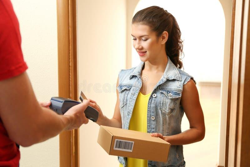 Junge Frau, die für das Paket empfangen vom Kurier zahlt stockbild