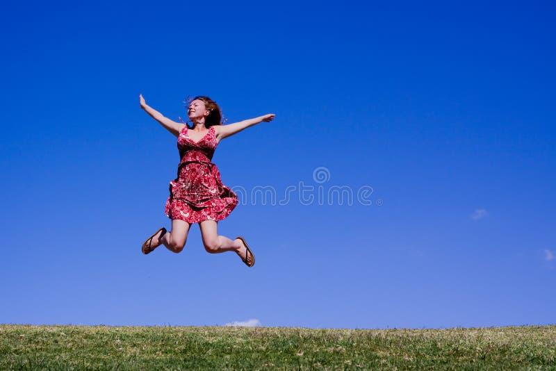 Junge Frau, die für Freude springt! lizenzfreie stockbilder