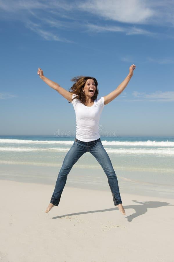 Junge Frau, die für Freude am Strand springt stockfoto