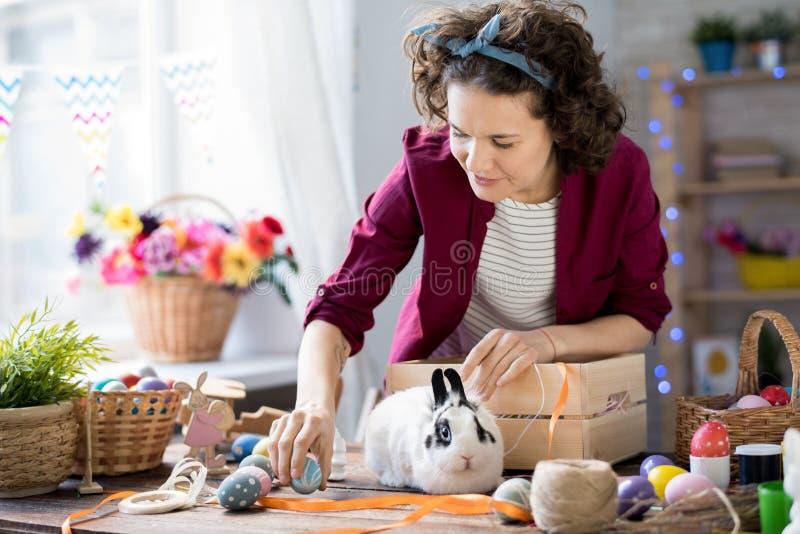 Junge Frau, die für Ostern sich vorbereitet stockfotografie