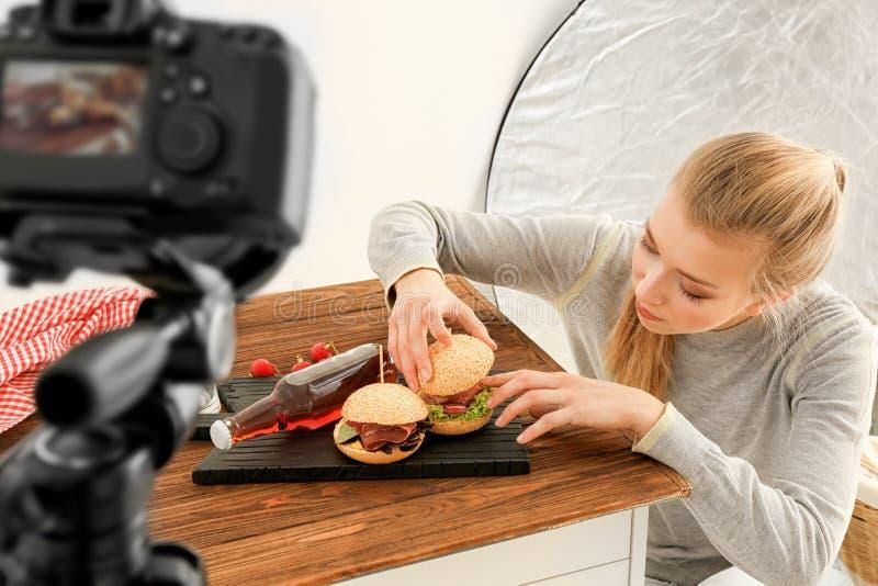 Junge Frau, die für schießendes Lebensmittel sich vorbereitet stockfoto