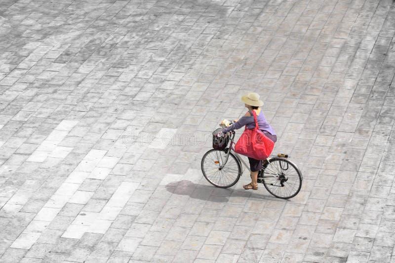 Junge Frau, die Fahrrad in der Straße, in der Sommerzeit und im Lebensstilkonzept fährt leerer Kopienraum stockfotografie