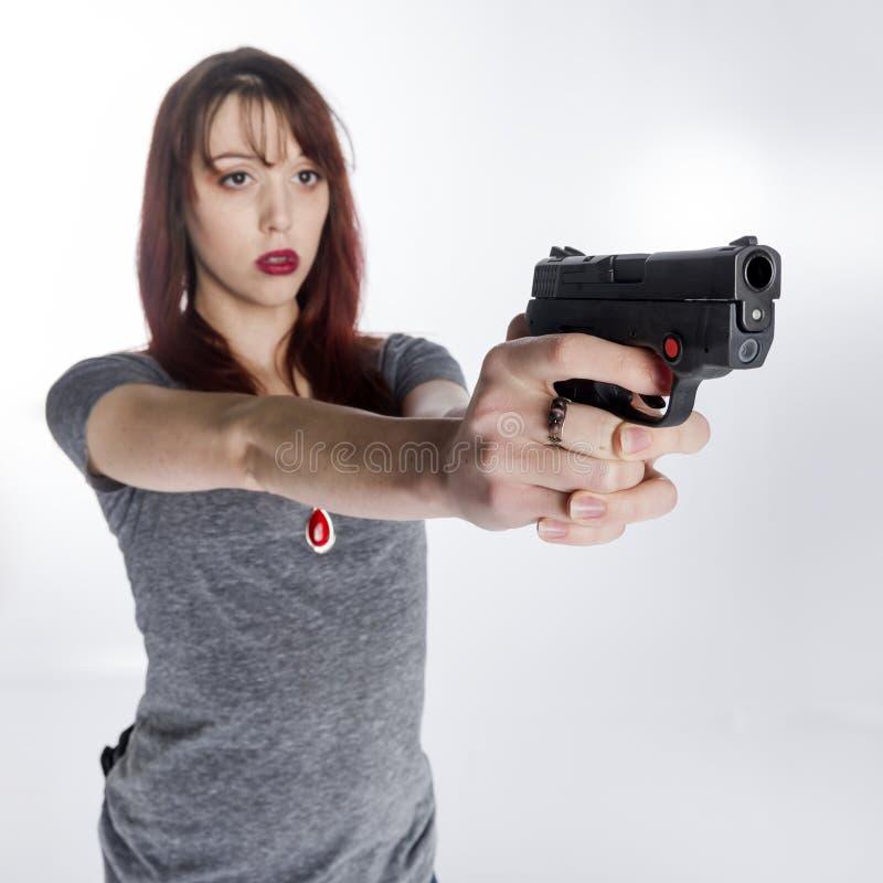 Junge Frau, die Faustfeuerwaffe mit beiden Händen hält lizenzfreie stockbilder